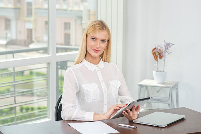 http://www.dreamstime.com/royalty-free-stock-photos-work-tablet-blonde-woman-works-your-tablet-looki-looking-camera-young-pretty-business-smiling-image40829558